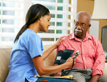 caregiver checks the vital signs of the old man