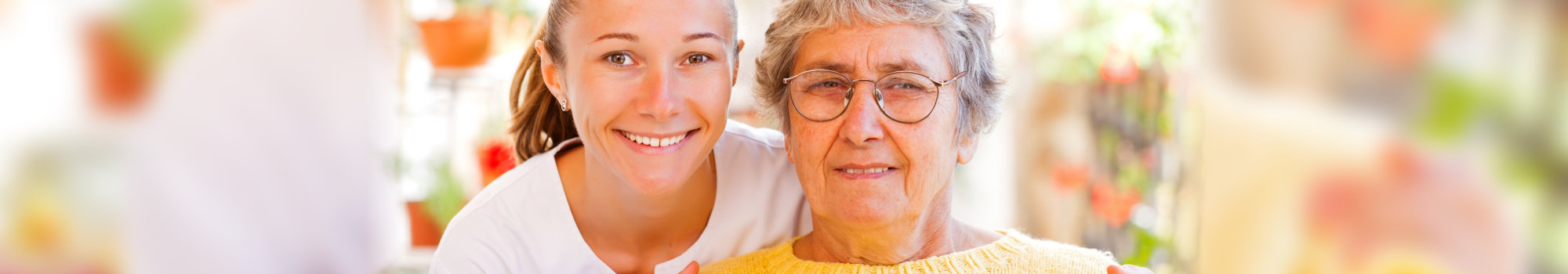 young woman and elderly woman smiling